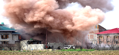 Smoke billowing out from house where militants were holed up at Chadoora area of Budgam district. -Excelsior/Shakeel