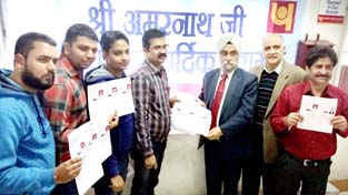 DGM PNB B S Raina handing over the registration permits to yatris at Jammu on Wednesday.
