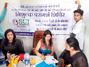 Dr Sunila Gupta writing prescription for a woman during free infertility health camp at R S Pura on Sunday.