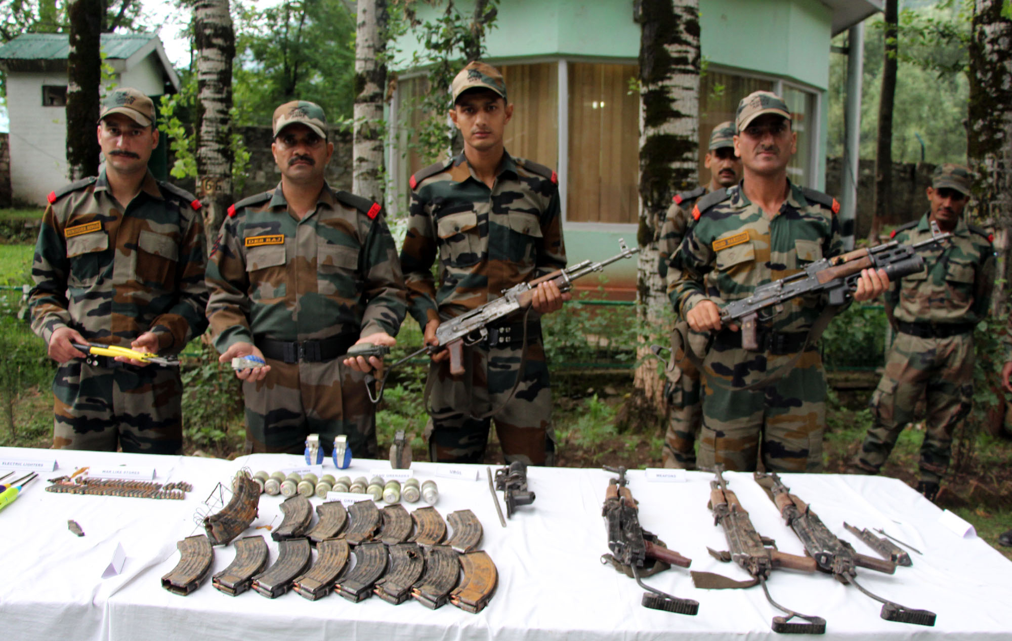 Army jawans display arms and ammunition recovered from killed militants in Uri on Sunday. — Excelsior/Aabid Nabi