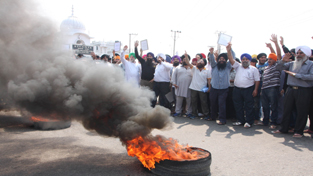 Sikh community members staging protest on highway outside Digiana Ashram in Jammu on Sunday.