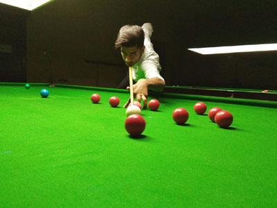 Cueist aiming at target during Snooker/Billiards Championship at MA Stadium in Jammu.