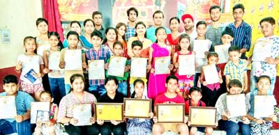 Winners of On Spot Painting Competition displaying certificates while posing for a group photograph in Jammu on Saturday.