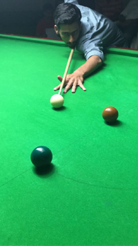 Cueist aiming at target during a match at Billiards Hall, MA Stadium in Jammu.