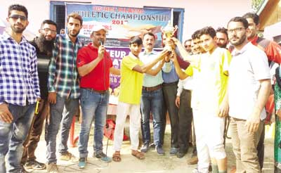 Winning team players receiving title trophy from the dignitaries.