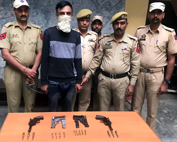 Top criminal in police custody with 4 weapons.