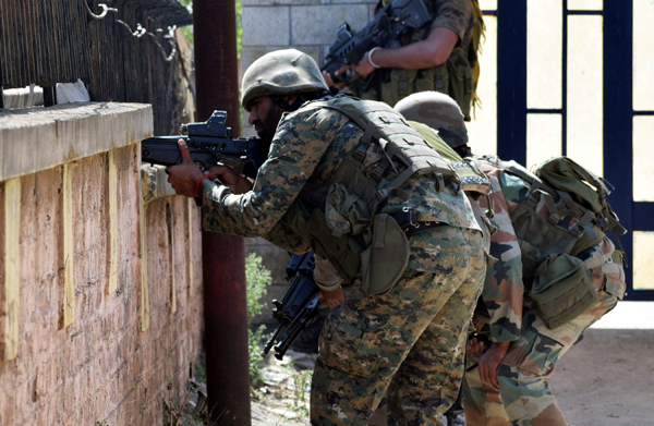Security personnel take positions during terror attack on BSF camp in Srinagar on Tuesday. — Excelsior/Shakeel