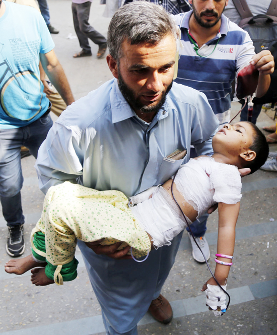 A man shifts his child injured in mortar shelling to the GMC Jammu on Monday. -Excelsior/Rakesh