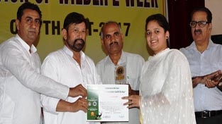 Minister for Forests, Ch Lal Singh presenting certificate to a participant of symposium at GDC Kathua on Saturday.