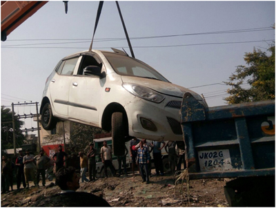 A wrongly parked car being lifted by a team of JDA officials at Transport Nagar, Jammu.