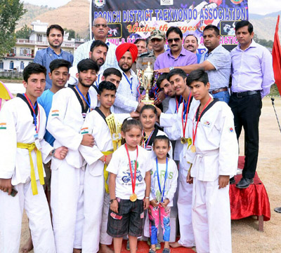 Winners of Taekwondo Championship posing along with dignitaries in Poonch on Monday.