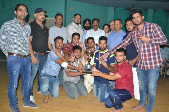 Winning team players receiving trophy from dignitaries.