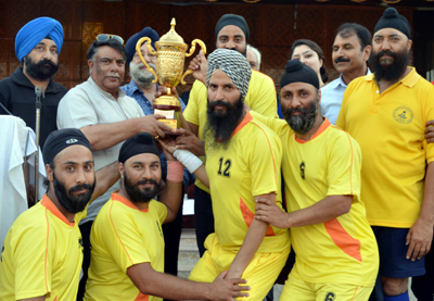 Jubilant players of Vikram Club Baramulla posing for a group photograph after winning Handball title.