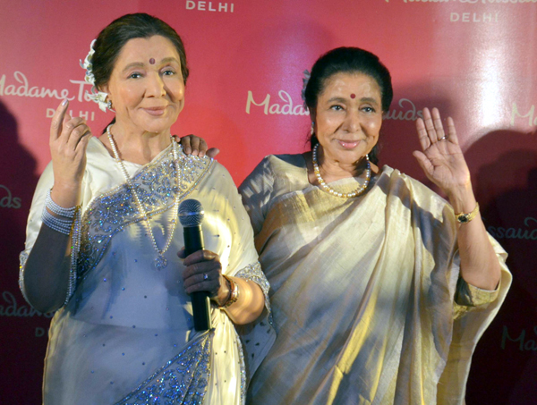 Legendary singer Asha Bhosle poses with her wax figure created by Madame Tussauds Delhi after unveiling it in New Delhi on Tuesday. (UNI)