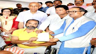 Deputy CM Dr Nirmal Singh handing over pension cheque to a beneficiary.