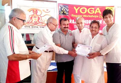 MLC, Vikram Randhawa presenting a certificate of merit during the conclusion of yoga camp at Jammu on Tuesday.