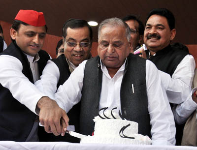 Samajwadi Party patriarch Mulayam Singh Yadav along with his son and the national president of the party during his 79th birthday celebration hosted by Akhilesh Yadav at party office in Lucknow on Wednesday. (UNI)