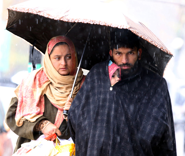 A couple takes cover under an umbrella during rains in Srinagar on Saturday. 	-Excelsior/Shakeel