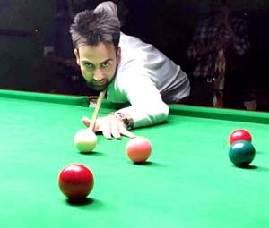 Cueist aiming at target in the final match of the State Senior Snooker Championship in Jammu.
