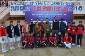 Young female cricketers posing along with dignitaries during Jammu Police Sports Festival on Tuesday.