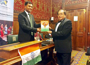 Major Gaurav Arya, a war veteran of India, receiving a book 'Don't Break Up India', from a leading businessman and philanthropist, Rami Langer, in UK Parliament.