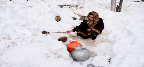 A woman fills her bucket with water after snowfall snaps water supply in upper reaches of South Kashmir. 	—Excelsior/Younis Khaliq