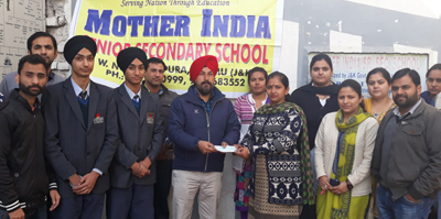 Principal of Mother India Senior Secondary School, Sonia Tohra, presenting cheque of Rs 21000 to maternal uncle of brain cancer affected child in the presence of staff and students.