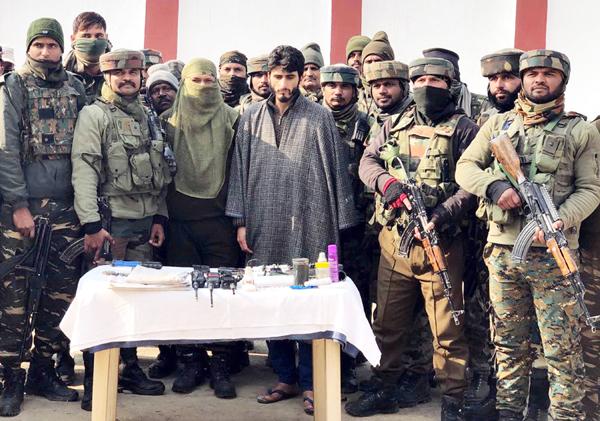 Affaq Ahmad Bhat in Army custody with recoveries in Handwara on Friday. (UNI)