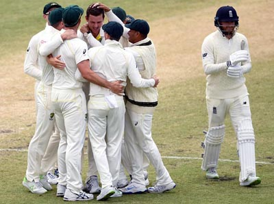 Australian players celebrate as Jonny Bairstow walks back after his dismissal.