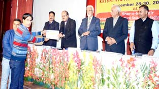 Scientist and Head of KVK Reasi, Dr Banarsi Lal receiving the presentation award during Zonal Workshop of KVKs organized at SKUAST-J.