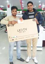 "Official of LG Electronics and customer showing prize won during 'LG Scratch Card"" offer."