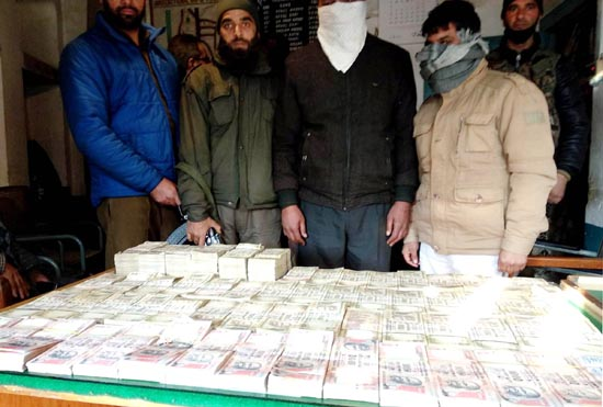 Accused in custody of police along with demonetized currency in Srinagar on Sunday. (UNI)