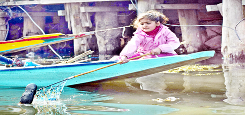 Little Kashmiri girl cleaning Dal lake. —Excelsior/Shakeel