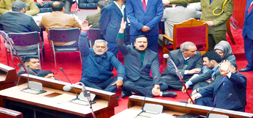 Opposition NC-Cong members staging protest dharna in 'Well' of Upper House in Jammu on Tuesday. -Excelsior/Rakesh
