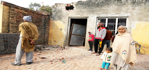 Border residents looking towards their damaged house after heavy shelling by Pakistan in R S Pura Sector.