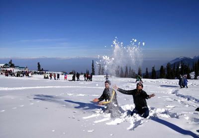 Tourists enjoying fresh snowfall at Gulmarg on Thursday.