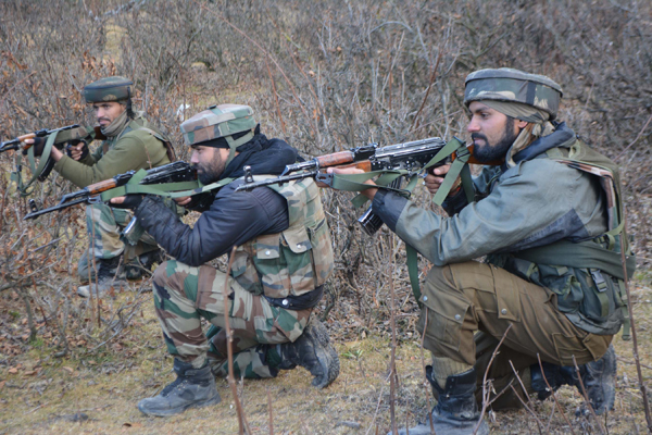 Security forces taking position during encounter with militants at Chaigund in Shopian district on Wednesday. —Excelsior/Younis Khaliq