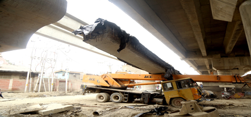 A girder falls on the crane at the construction site of Rambagh flyover in Srinagar during earthquake on Wednesday. —Excelsior/Shakeel