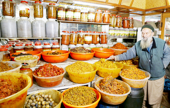 A shopkeeper arranges pickles in his shop at Srinagar. -Excelsior/Shakeel