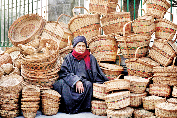 An elderly man waits for customers at his roadside stall selling cane baskets in old city of Srinagar on Tuesday. -Excelsior/Shakeel