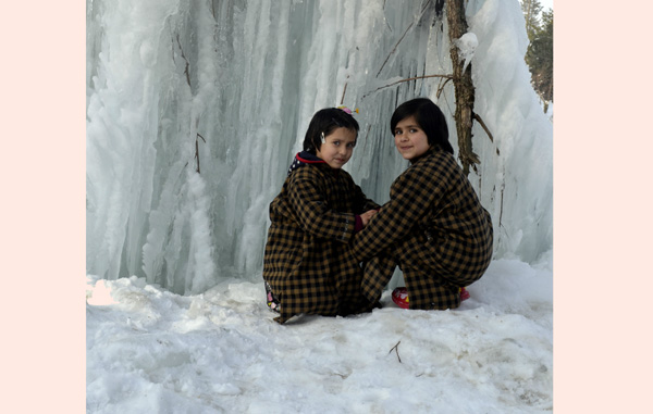Girls try to touch icicles in Tangmarg area of Gulmarg in Baramulla district. —Excelsior/Aabid Nabi
