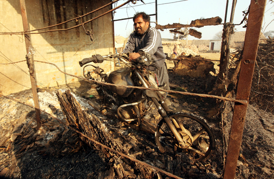 A man tries to remove remnants of his burnt motorcycle in Jeora Farm of R S Pura Sector, where number of 'Kullahs' were gutted in Pakistan shelling on Saturday.