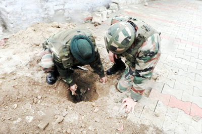 Army jawans digging out unexploded mortar shell in village Bhour Jagir of tehsil Akhnoor.