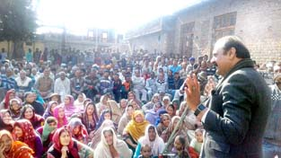 NC leader Surjit Singh Slathia addressing a public meeting at village Trindian in Ramgarh on Sunday.