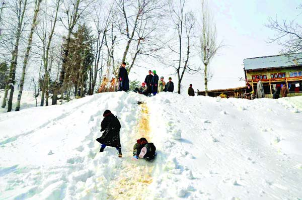 Children playing sledges on snow covered hilly road on the outskirts of Srinagar. —Excelsior/Shakeel