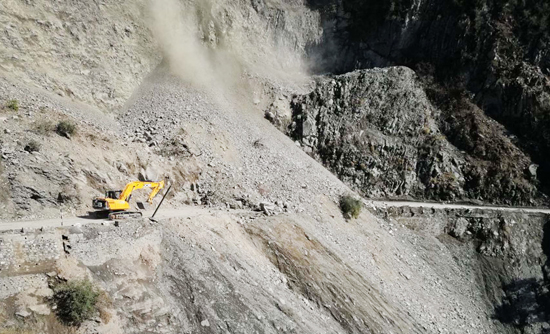 A JCB clearing highway near Ramsoo in Ramban area on Wednesday. (UNI)