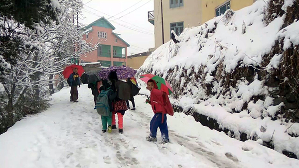 Children making way to their school amid snowfall in Bhaderwah on Tuesday morning. (UNI)