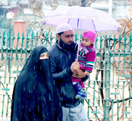 A couple with kid, under one umbrella moves along road during rain in Srinagar on Saturday. —Excelsior/Shakeel
