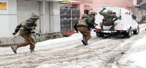 Security personnel taking position at Karan Nagar, Srinagar during encounter on Monday. (UNI)