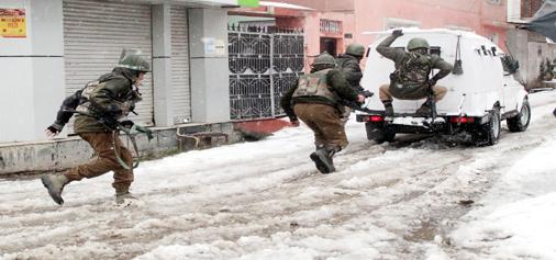 Security personnel taking position at Karan Nagar, Srinagar during encounter on Monday. (UNI)